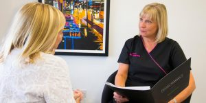 Dentist offering patient follow up care after dental implant surgery