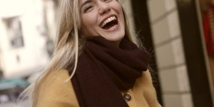 A young women dressed for winter shows off the perfect smile
