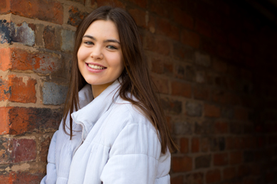 Isabella showing her new smile after having fixed braces for teenagers